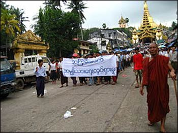 """Saffron Revolution protestors in Yangon carrying a banner that reads """"Non-Violence: National Movement"""" in 2007 – Photo: Wikipedia"""