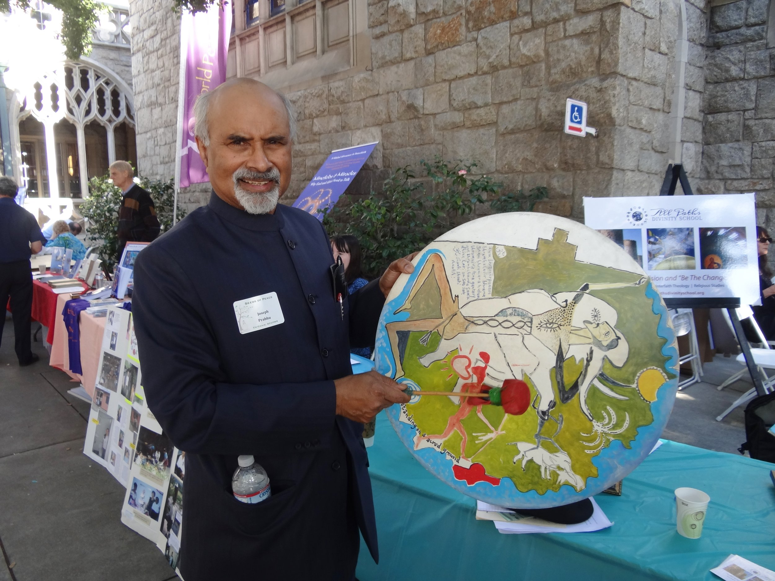 "Professor Prahbu holding a ""Mankind"" initiation drum, painted by artist   Andre van Zijl, at a Seeds for Peace conference in Pasadena, California, sponsored by the Southern California Council of the Parliament of the World's Religions. – Photo: Ruth Broyde Sharone"