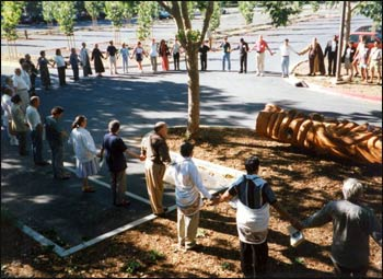 Those attending a 1997 planning conference for United Religions Initiative gathered for a circle of blessings as they began work, blessings said around a beautiful whale carved from a massive Alaskan cedar, felled nearly a century ago. – Photo: Don Frew