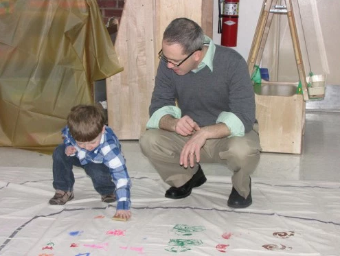 David Joyal and his son, Aidan, stamp patterns on the path of a labyrinth as part of an intergenerational project. Photo: Sharon Sheridan