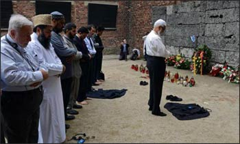 Muslim religious leaders from across the globe pray in front of so-called death wall at the Nazi death camp Auschwitz-Birkenau as part of an anti-genocide program on May 22, 2013. Muslim religious leaders from across the globe met with Holocaust survivors in an emotional encounter at Warsaw's synagogue, as part of an anti-genocide program that includes a visit to Auschwitz. Photo: Janek Skarzynski, AFPO
