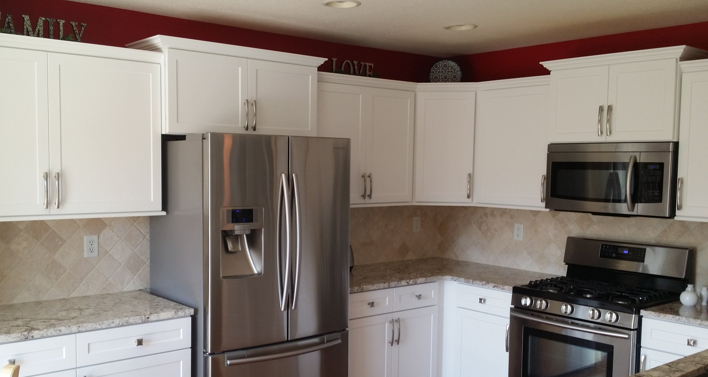 Replacing standard cabinet sizes with a larger cabinet above the microwave and or fridge can give a simple kitchen a much more dramatic look if you have space for it. This photo also features crown moulding, under cabinet trim, and full overlay spacing.