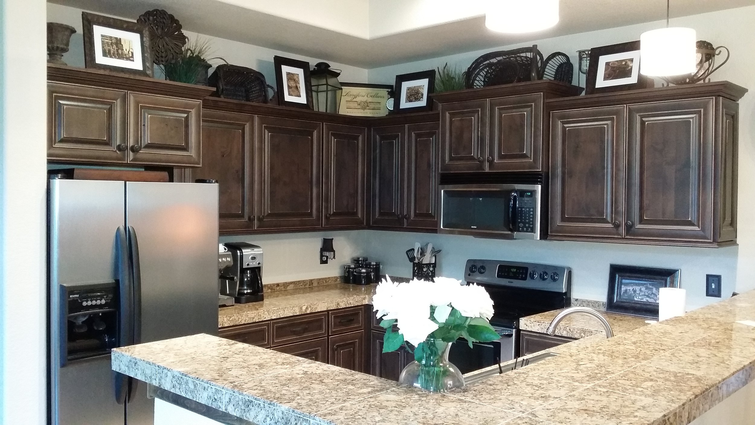 This traditional craftsman style kitchen features over sized micro and fridge cabinets with crown moulding and under cabinet trim. It also has full overlay spacing and a rub through finish.