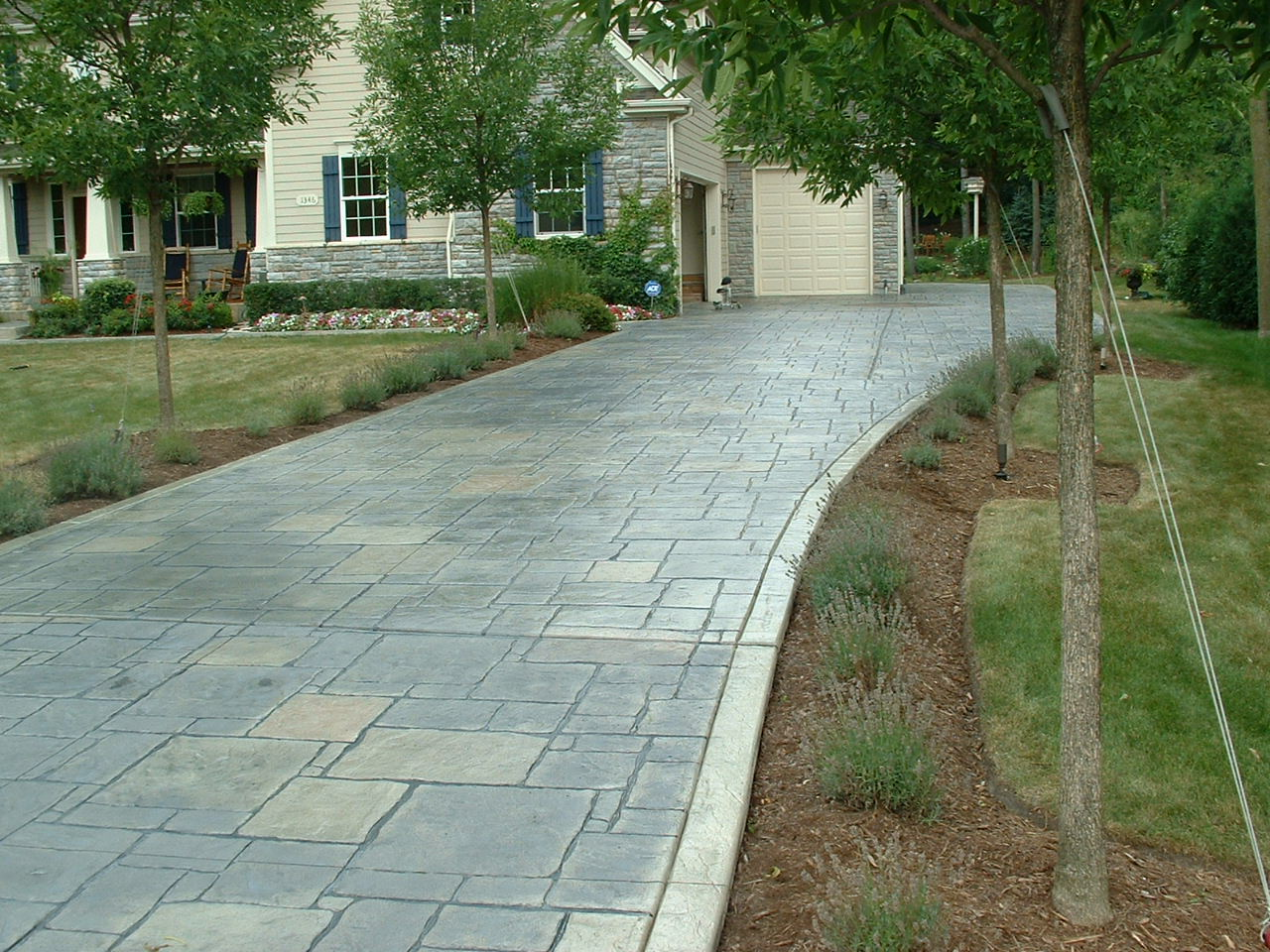 """This was a badly damaged driveway from neglect and salt over the years. Powerwashed, patched holes, used Brickforms 1/4"""" Stampable Overlay to fix the stone pattern. Brickforms colors were used in additon to Brickforms Solvent Based Sealer Gem-Seal."""