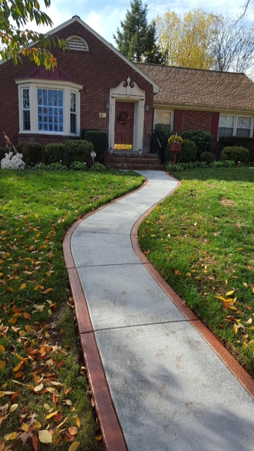 This winding walkway is simple, yet makes a huge difference to the homes curb appeal.  We simply accented Brick Red color in the border!