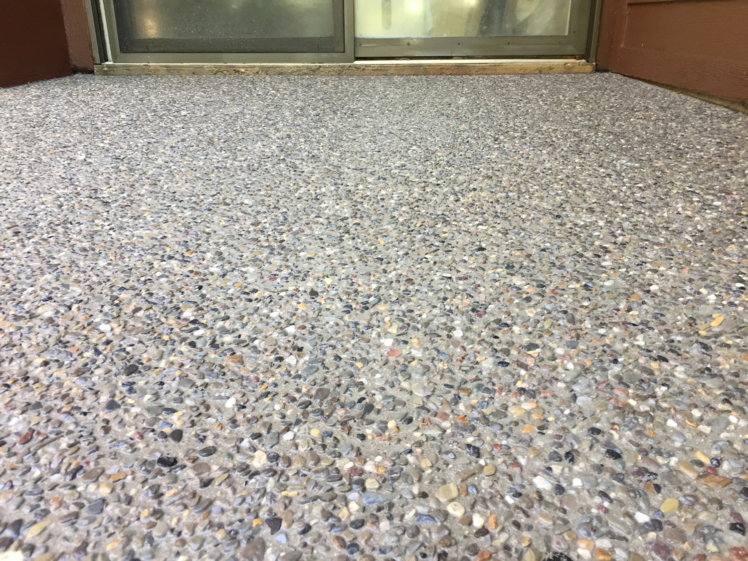 This picture shows an exposed aggregate patio, using Brickform SSD. The stone is a river jack pea gravel.