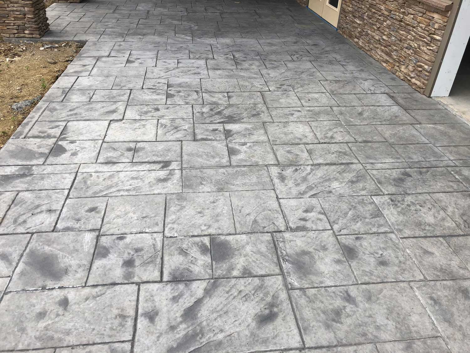 Large Ashler slate stamp featuring the blue stone texture. Standard non colored redi mix concrete. Dark grey antique-it. Gem cure and seal.