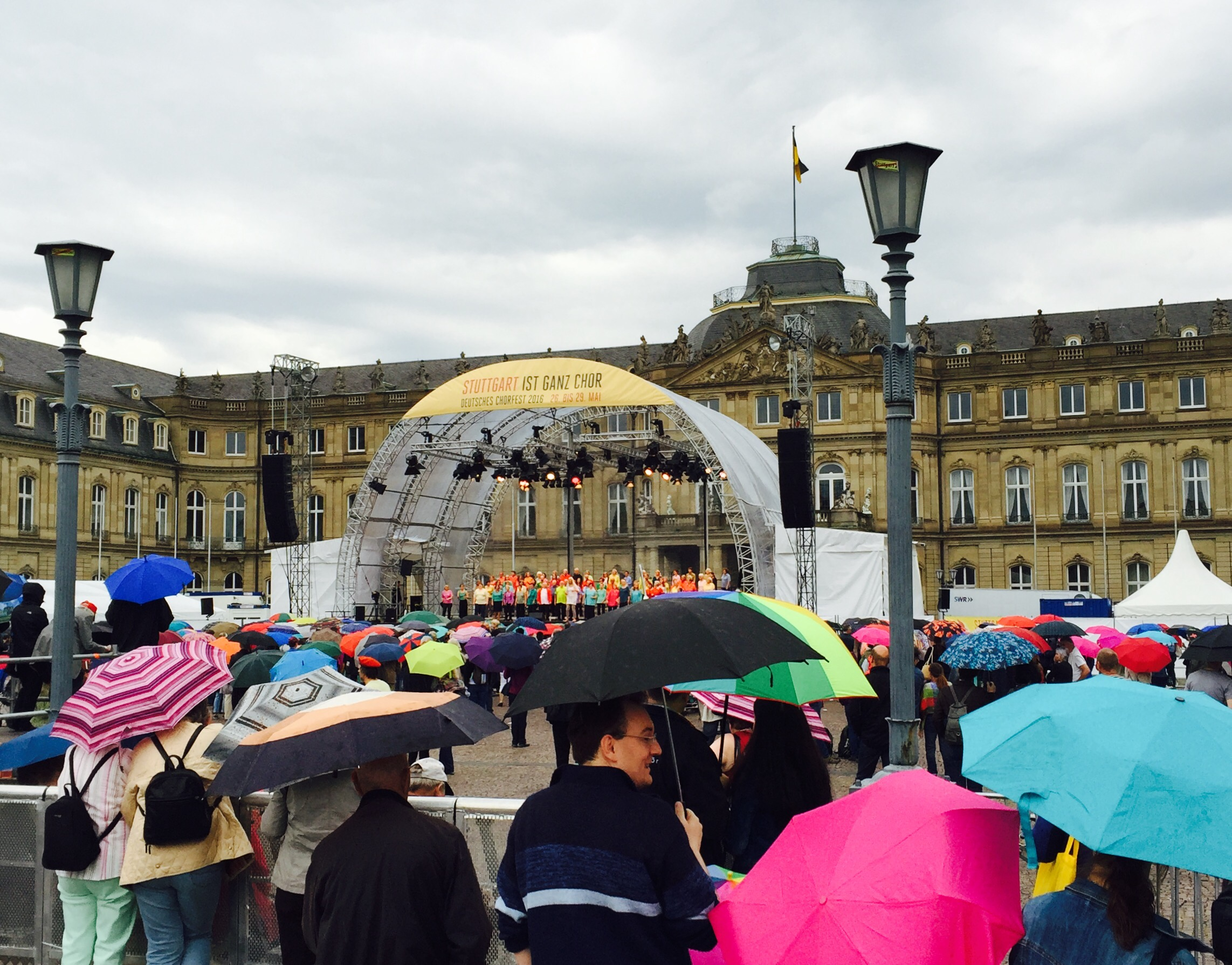 A large crowd listens to choral music standing in the rain.