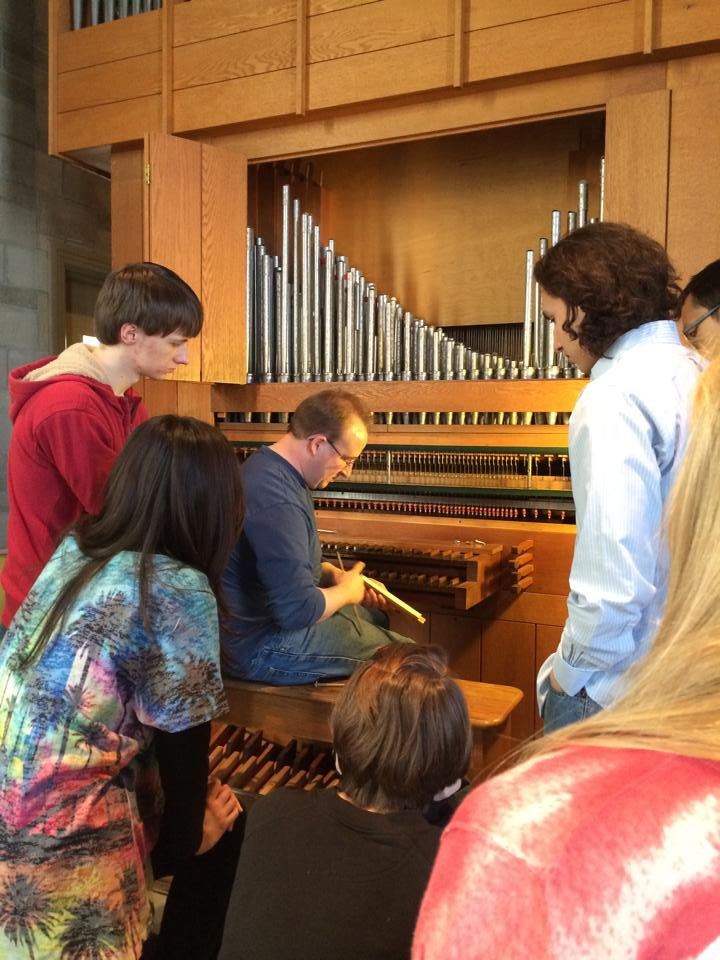 Students learn from a pipe organ builder.