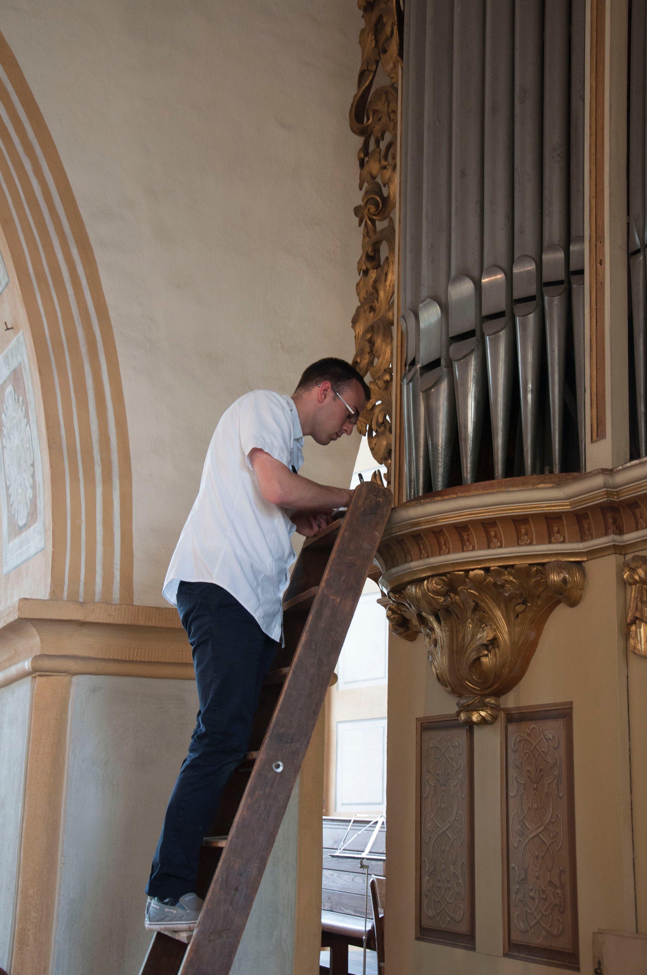 Kade Phillips noting pipe measurements of a Silbermann Organ in Rötha, Germany, in 2016.