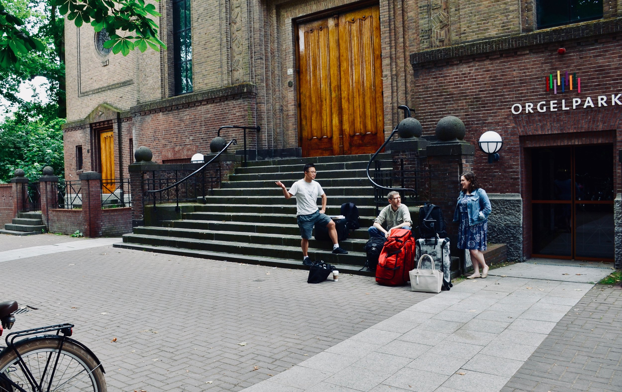 Adrian Cho, Chris Porter, and Chelsea Keating chat outside Orgelpark in Amsterdam.
