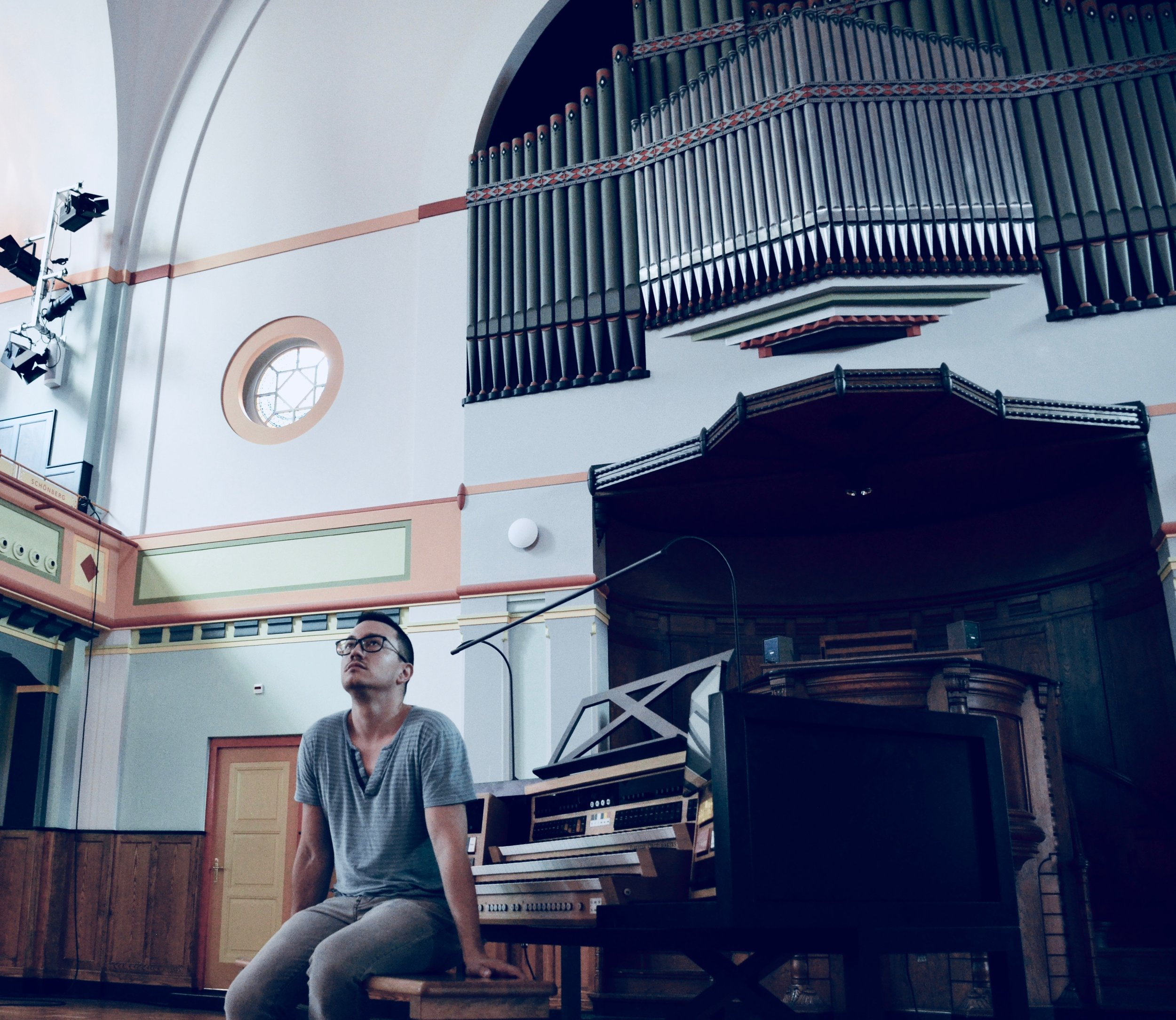Corey De Tar listens intently, with the façade of the Sauer organ at Orgelpark behind.