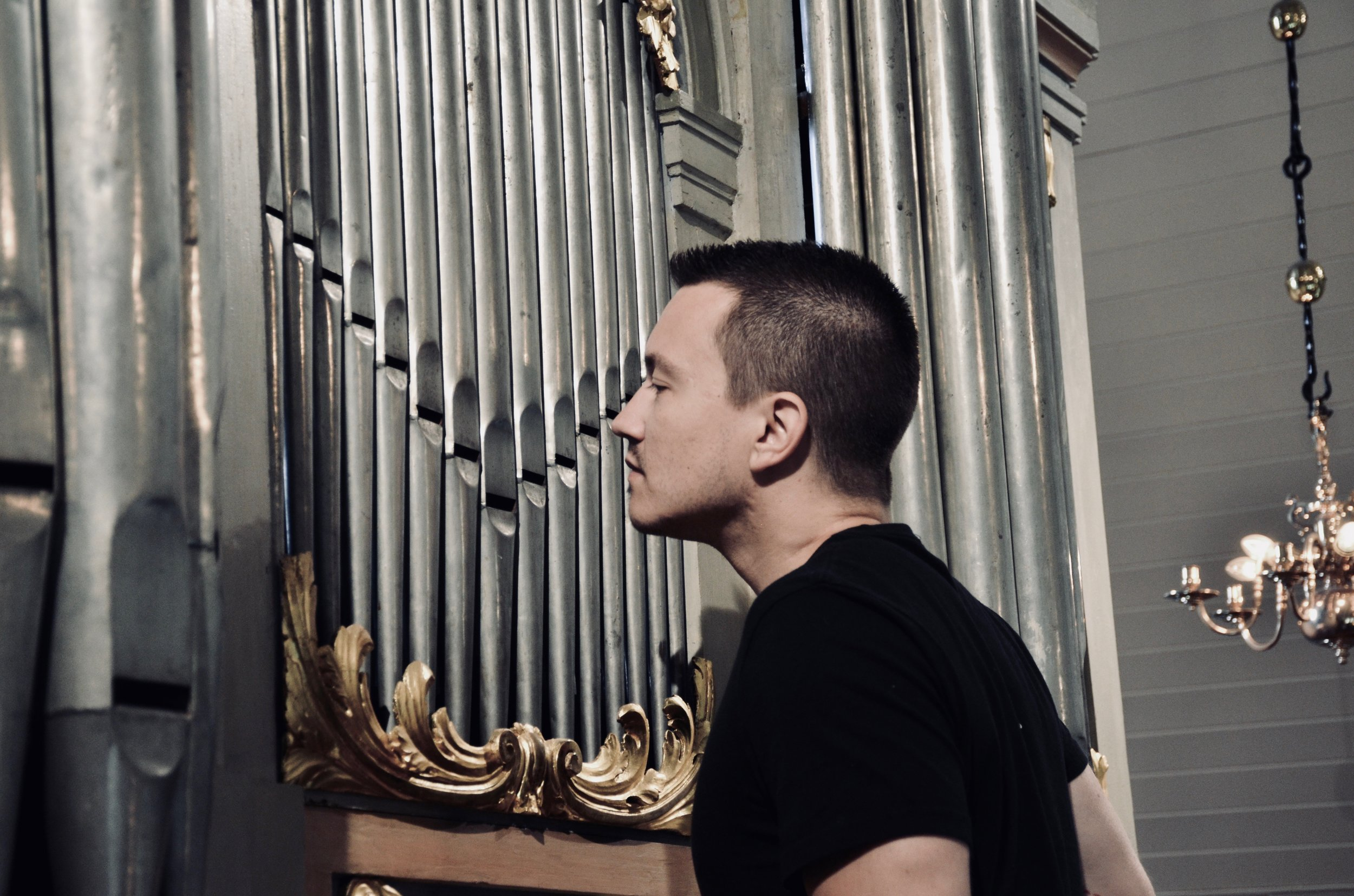Corey De Tar examines the pipe construction of the 1783 Schiörlin organ in Jonsered, Sweden.