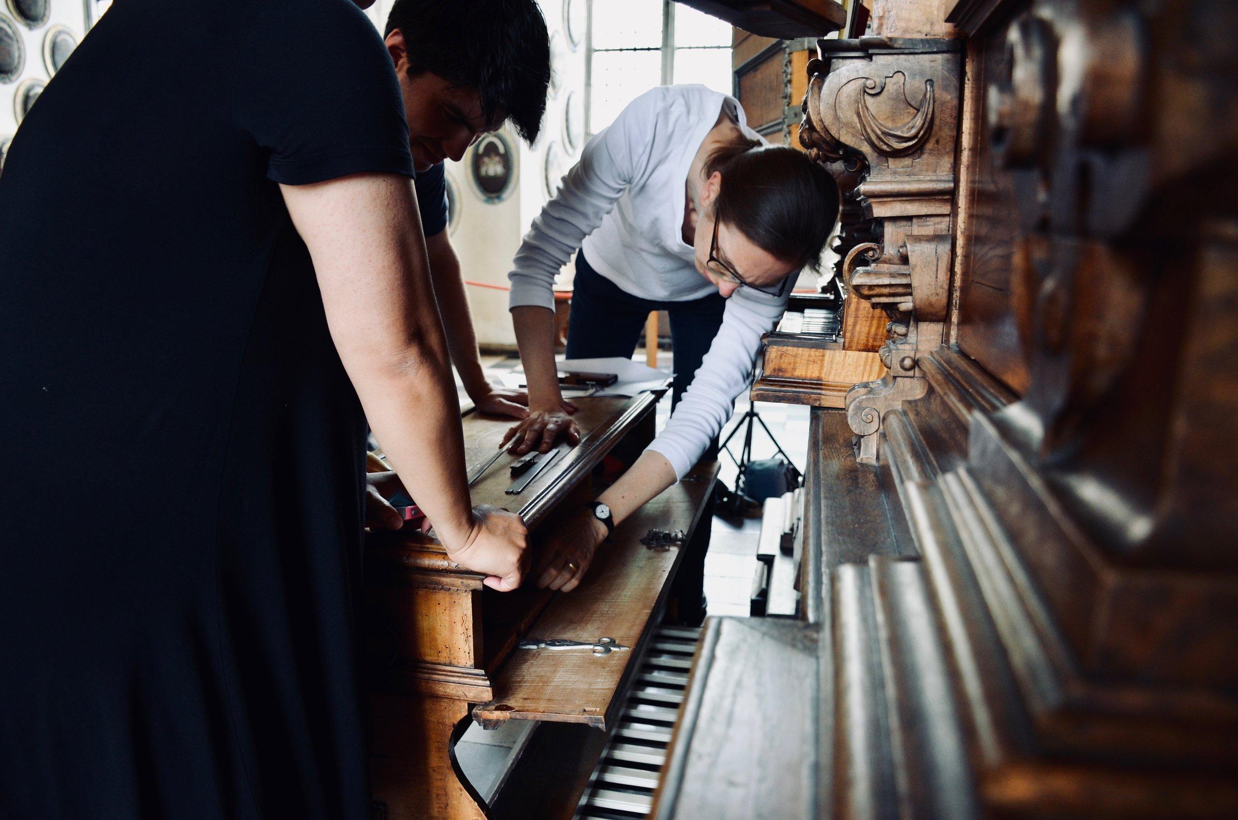 Castle organist Bine Bryndorf opens the bench compartment, 1610 Compenius organ, Frederiksborg Castle, Hillerød, Denmark.