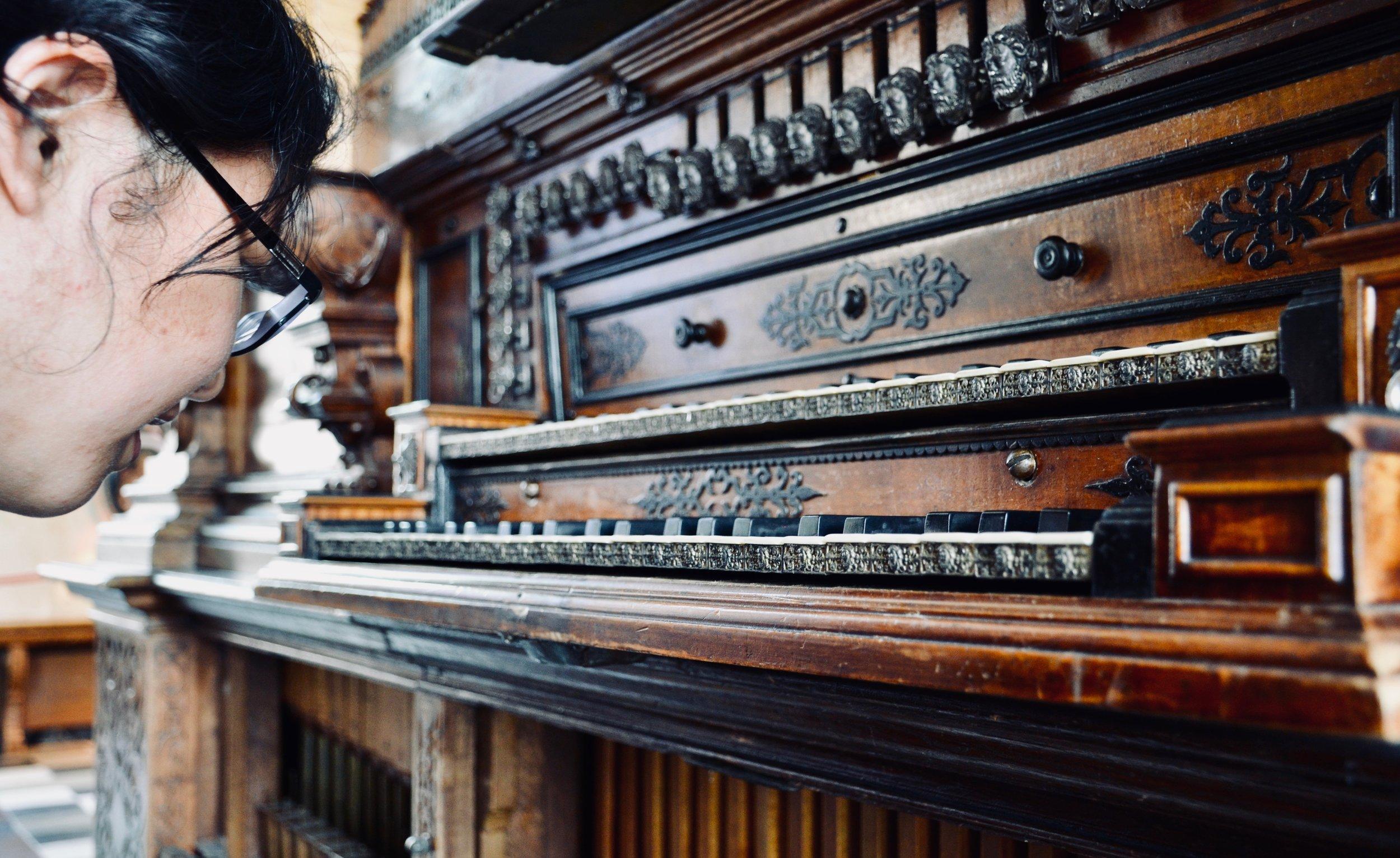 Jennifer Hsiao admires the keyboard carvings, 1610 Compenius organ, Frederiksborg Castle, Hillerød, Denmark.
