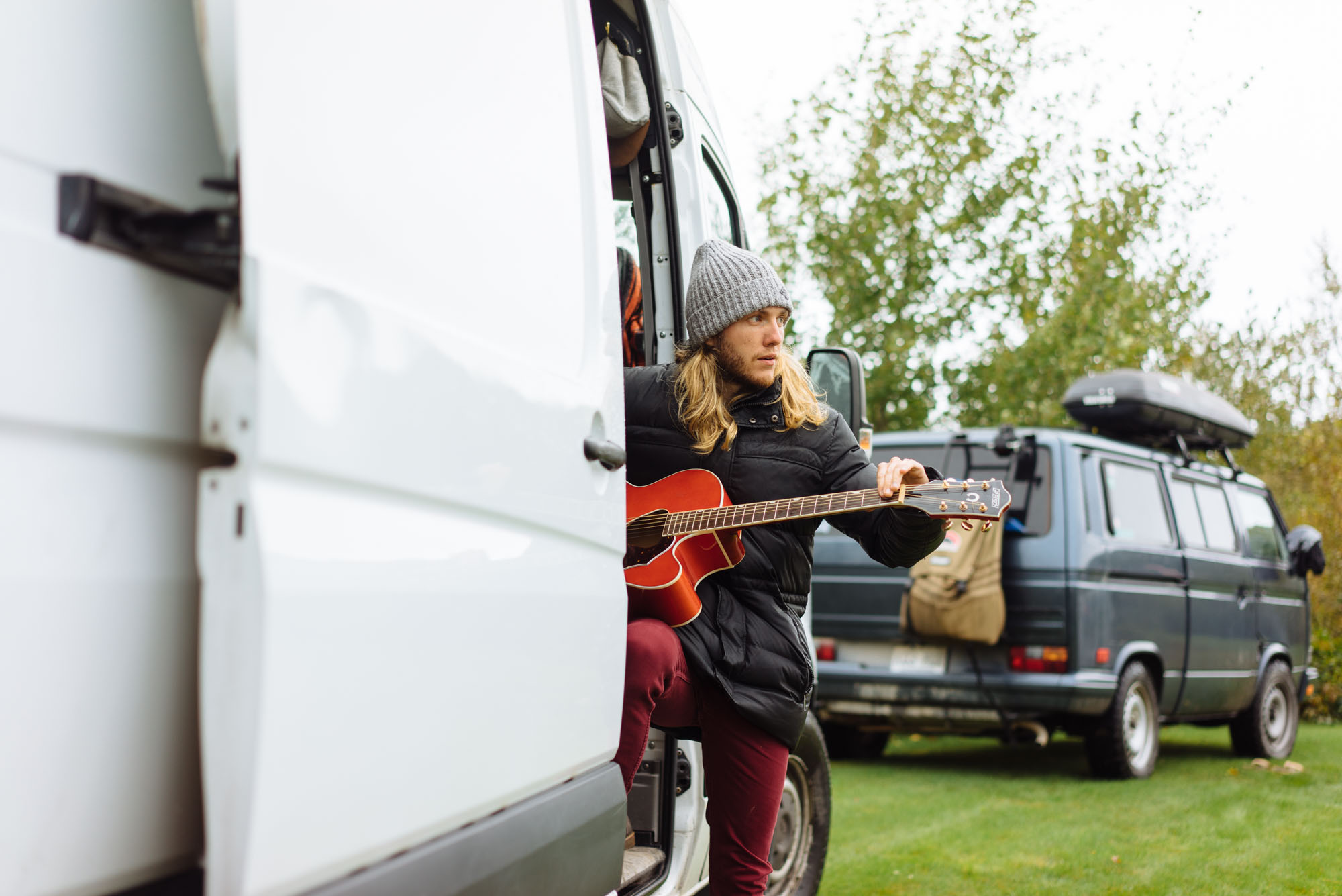 Anthony playing his guitar in his van