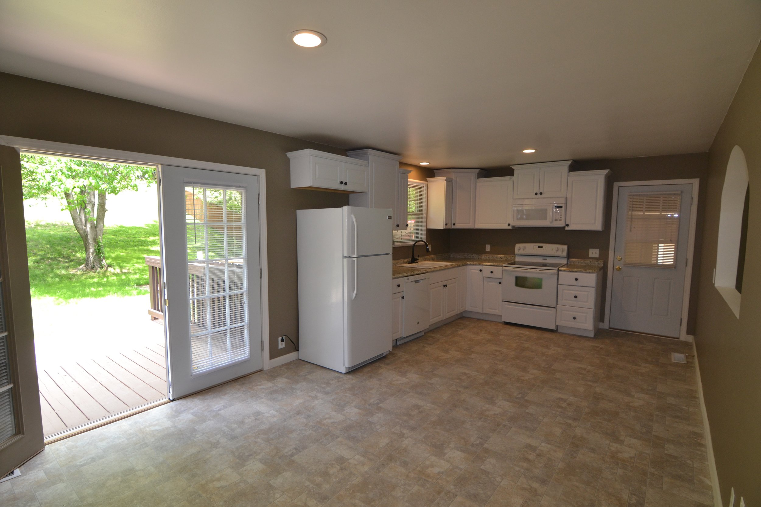 Spacious kitchen with New double french doors leading to 10x30 ft Deck overlooking beautiful Landscaped back yard with Privacy fence