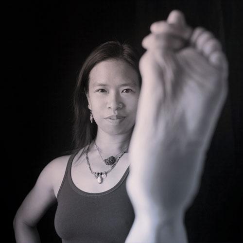 "Amy ""PRIYA"" Santos directs our ashtanga program. She is authorized level 2 by Guruji Sri K. Pattabhi Jois to teach the Ashtanga Yoga Method."