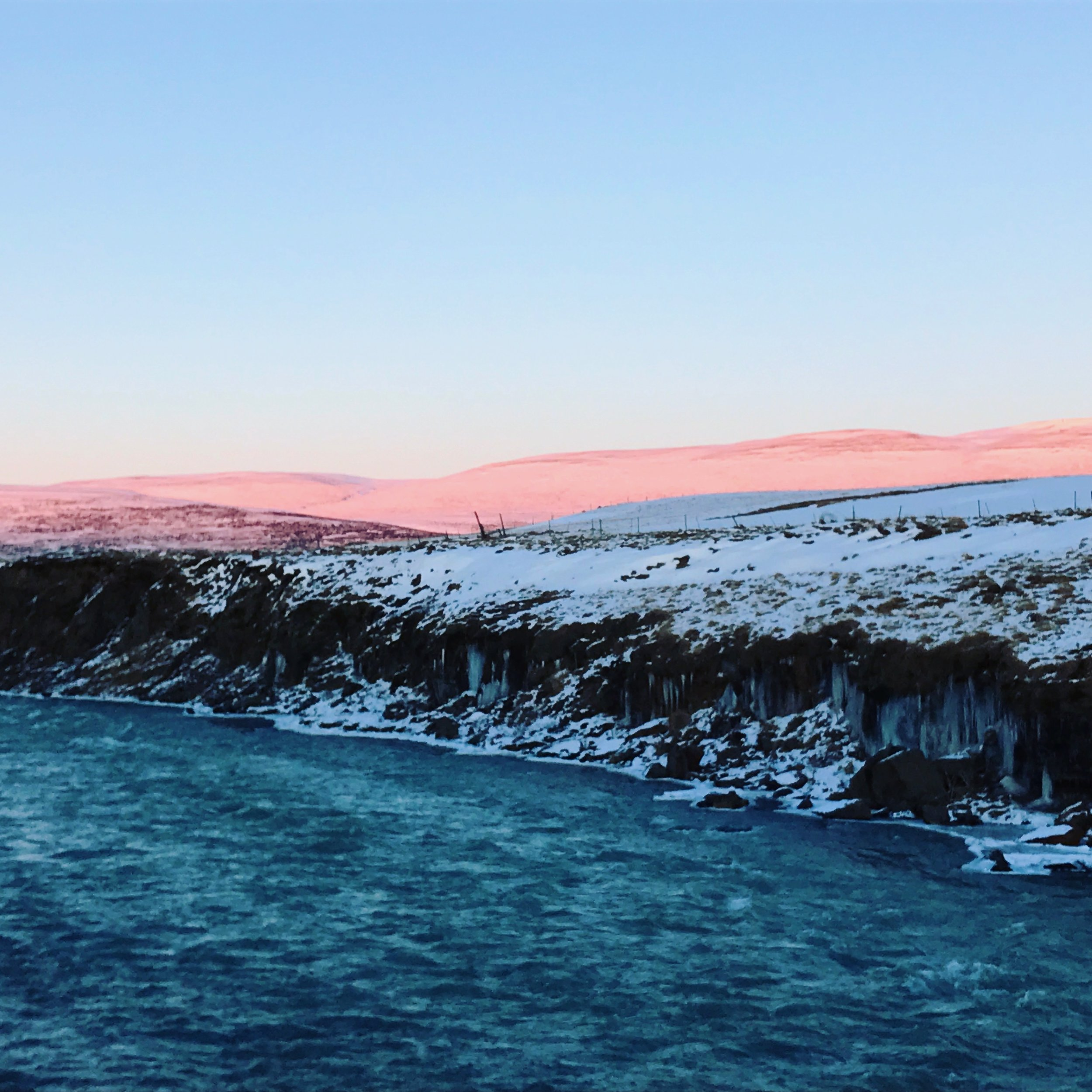 The mountains turn a beautiful pink as the sun begins to set, view from Hrútey Island.