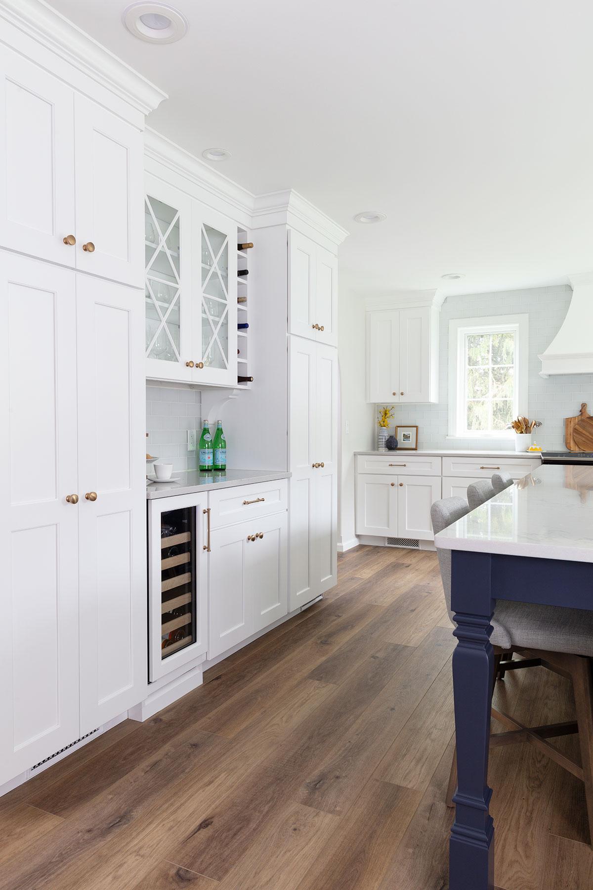 white kitchen with blue island wine bar
