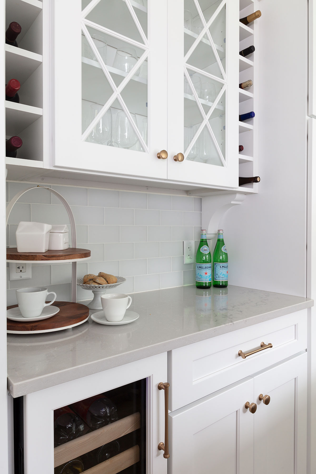 white kitchen with blue island glass cabinets and wine storage