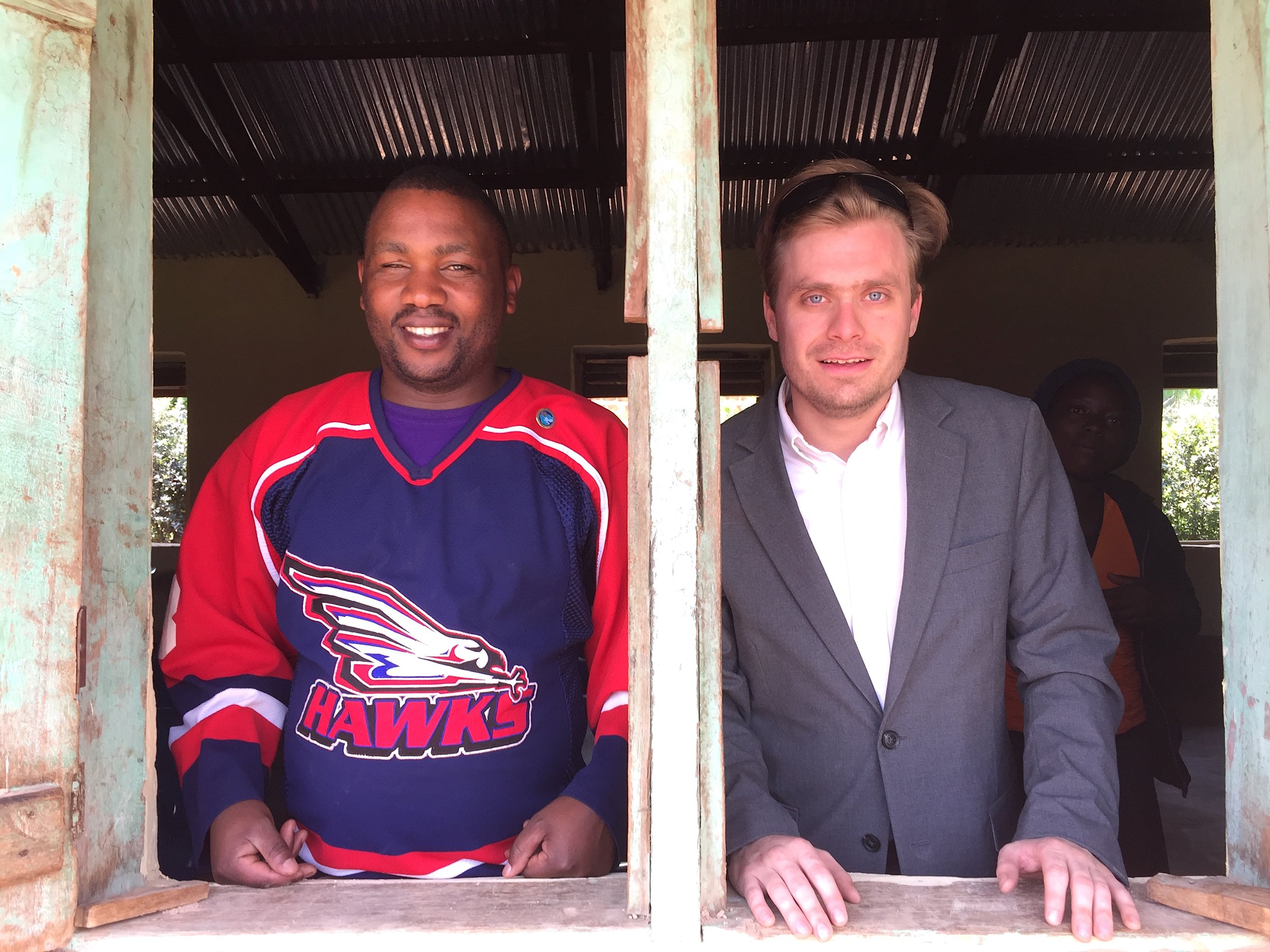 Guma and Evan looking out classroom windows at Muko High School.