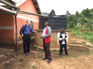 Dave Molzahn of Midland, MI confers with Alexander Gumoshabe, ACT's Senior Manager about the water supply at the High School.