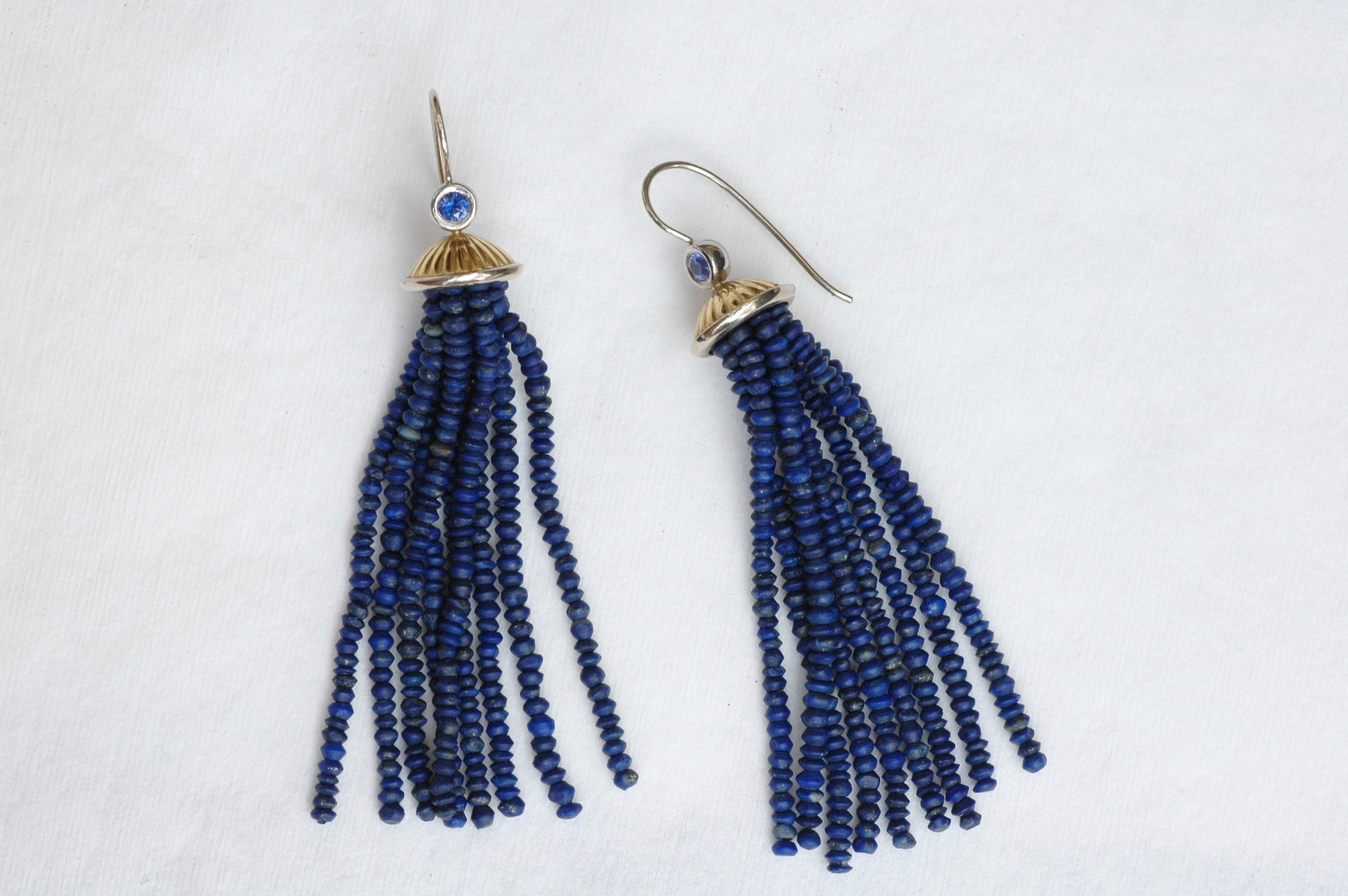 Tassel earrings by Gregore  with Afghanistan lapis lazuli beads strung onto 18k yellow and white gold earring tops, accented with  blue sapphires