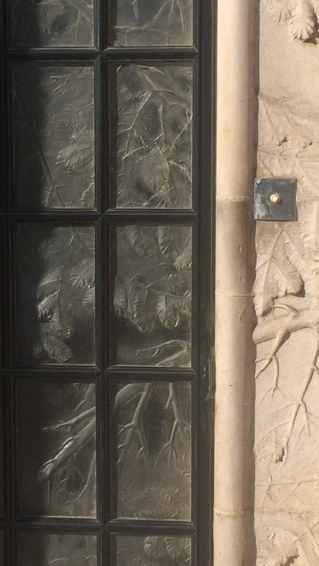 In Paris near the Seine René Lalique had an apartment. The door fit his style, the concrete cast edging of branches and leaves transitioned into carved, cast glass door panels with the same motif.