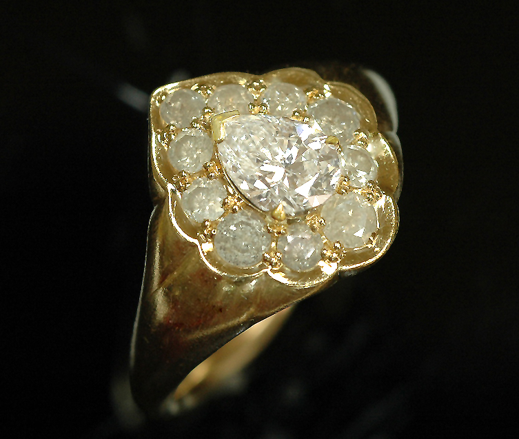 Engagement Ring in !8 karat yellow gold, set with small opaque white diamonds, and a center pear shaped diamond.
