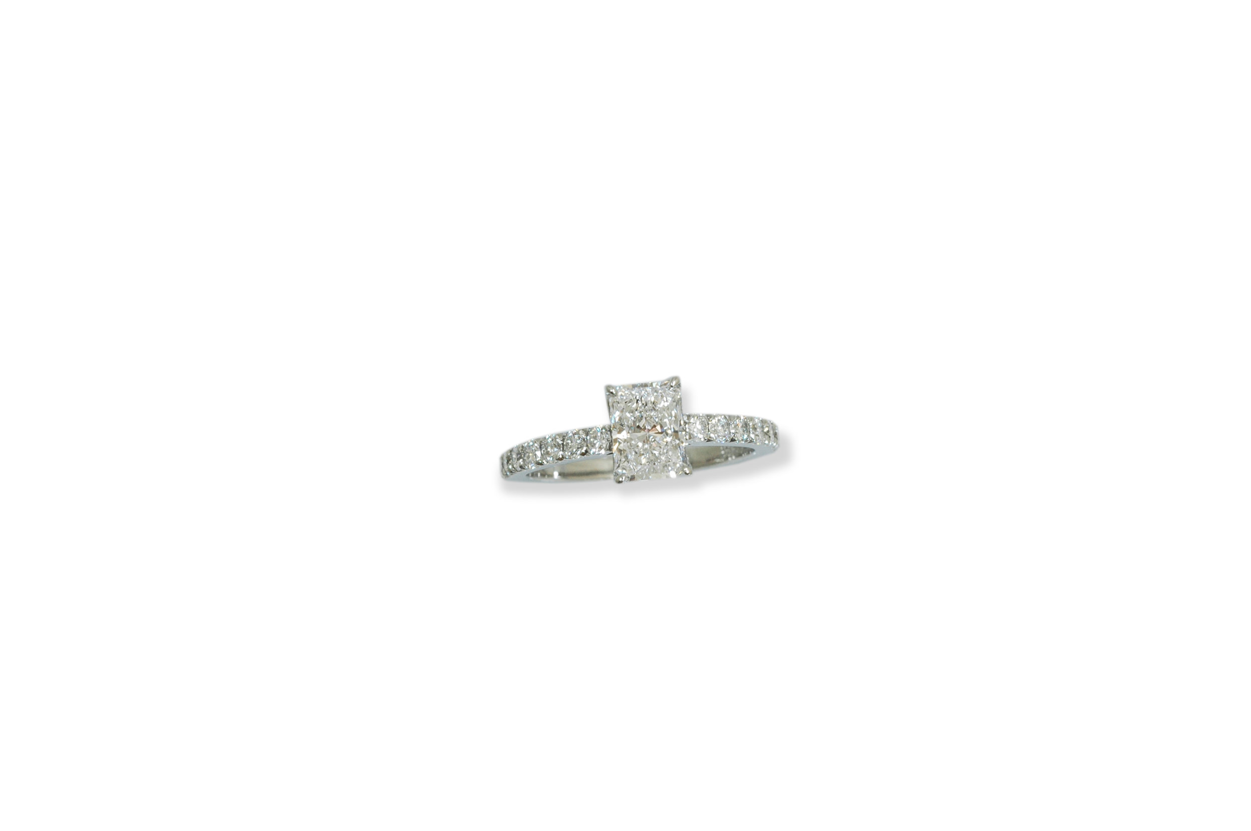 Engagement ring in platinum with a radiant cut Diamond in the center and brilliant cut diamonds on the band.