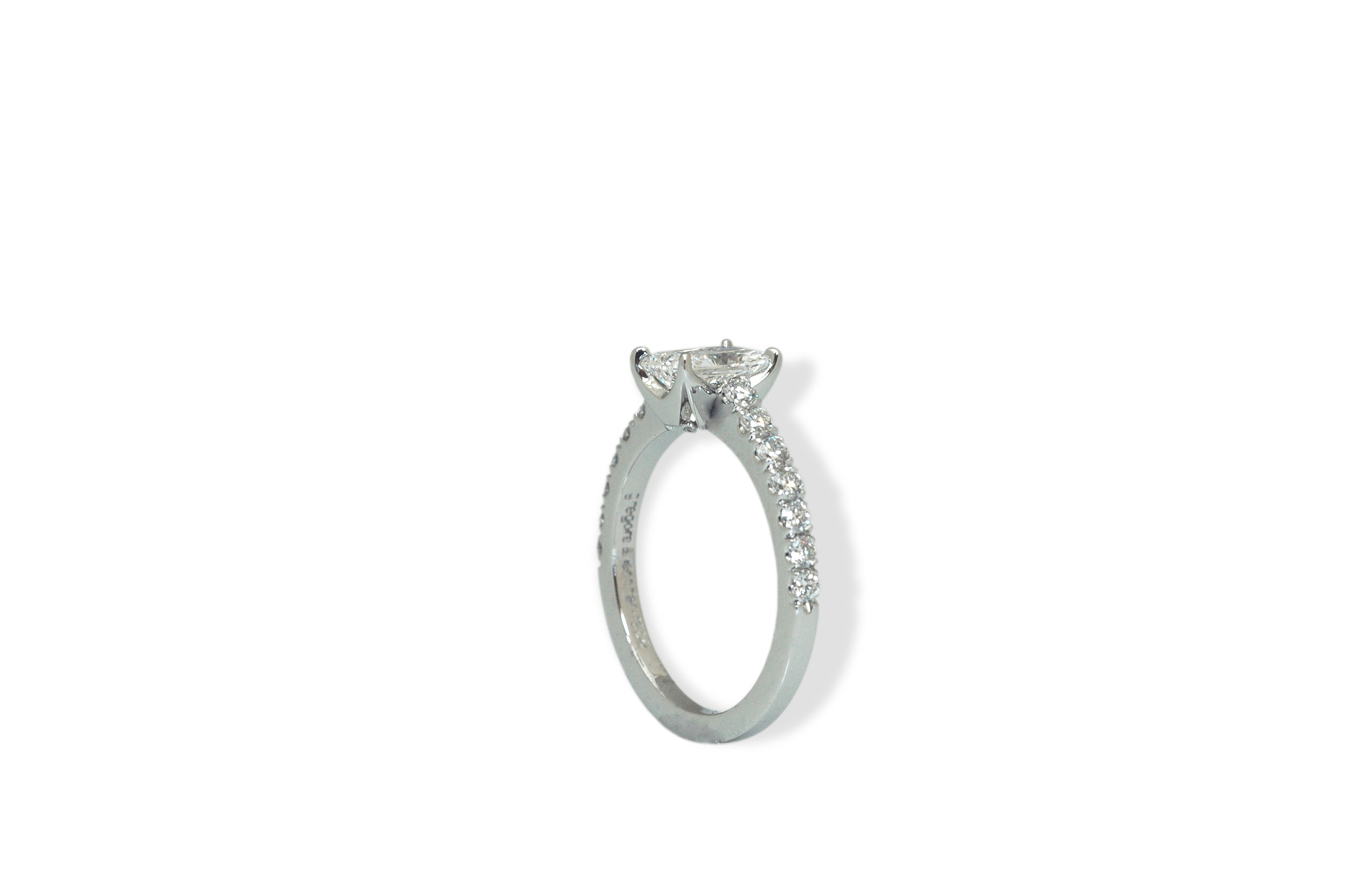 Engagement ring in platinum and diamonds with accent diamonds at the base of the center setting.