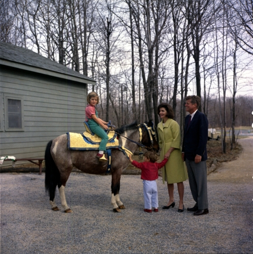 President John F Kennedy and his family watch daughter Caroline ride a horse named 'Tex' at Camp David. From left: Caroline, John F. Kennedy Jr., First Lady Jackie Kennedy and President Kennedy. (Photo Courtesy: National Archives)