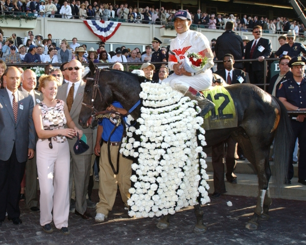 Adorned with the winner's traditional blanket of carnations, Sarava and his team celebrate winning the 2002 Belmont Stakes.