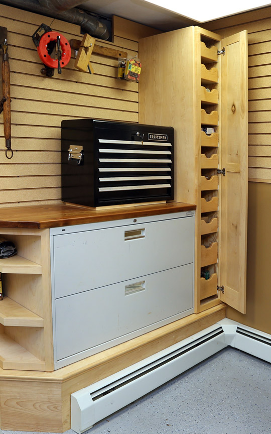 The tall cabinet opens to reveal a number of small drawers for housing small boxes of screws, nails, and other hardware.