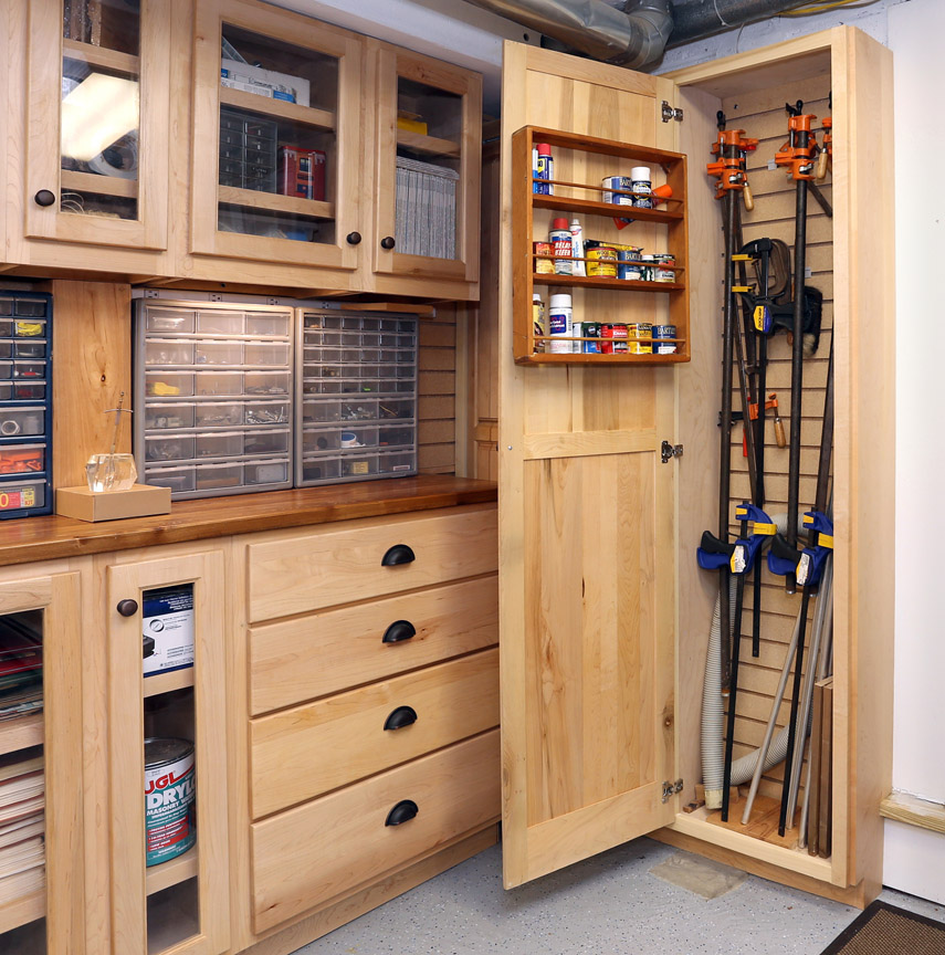 The tall wall cabinet provides storage for longer items like clamps and sections of pipe. All the pulls and handles on the cabinet doors and drawers are in a weathered bronze finish.