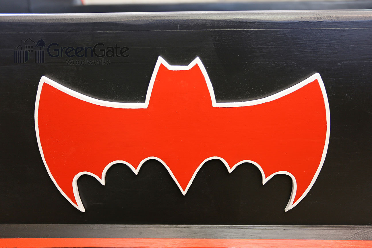 A closeup of the Bat logo on the side rail of the bed.