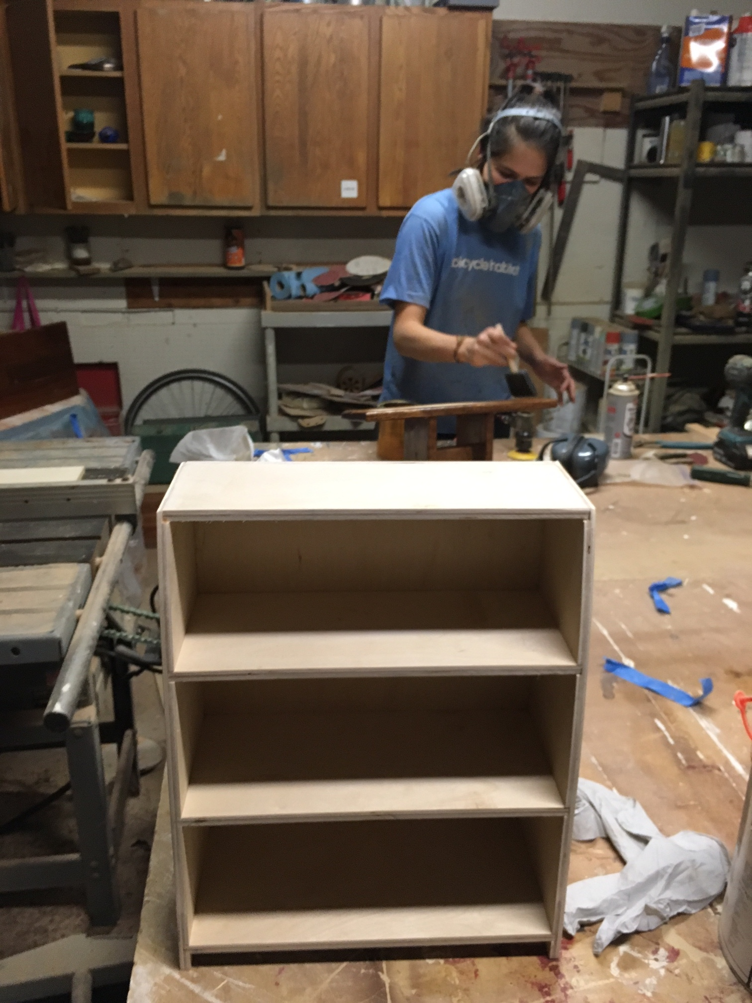 Spice rack just before being stained and sprayed. Really simple construction, just a few dados and rabbets, plus a gentle curve on the sides. Kristina is in the background brushing polyurethane onto one of our meditation stools that just sold.