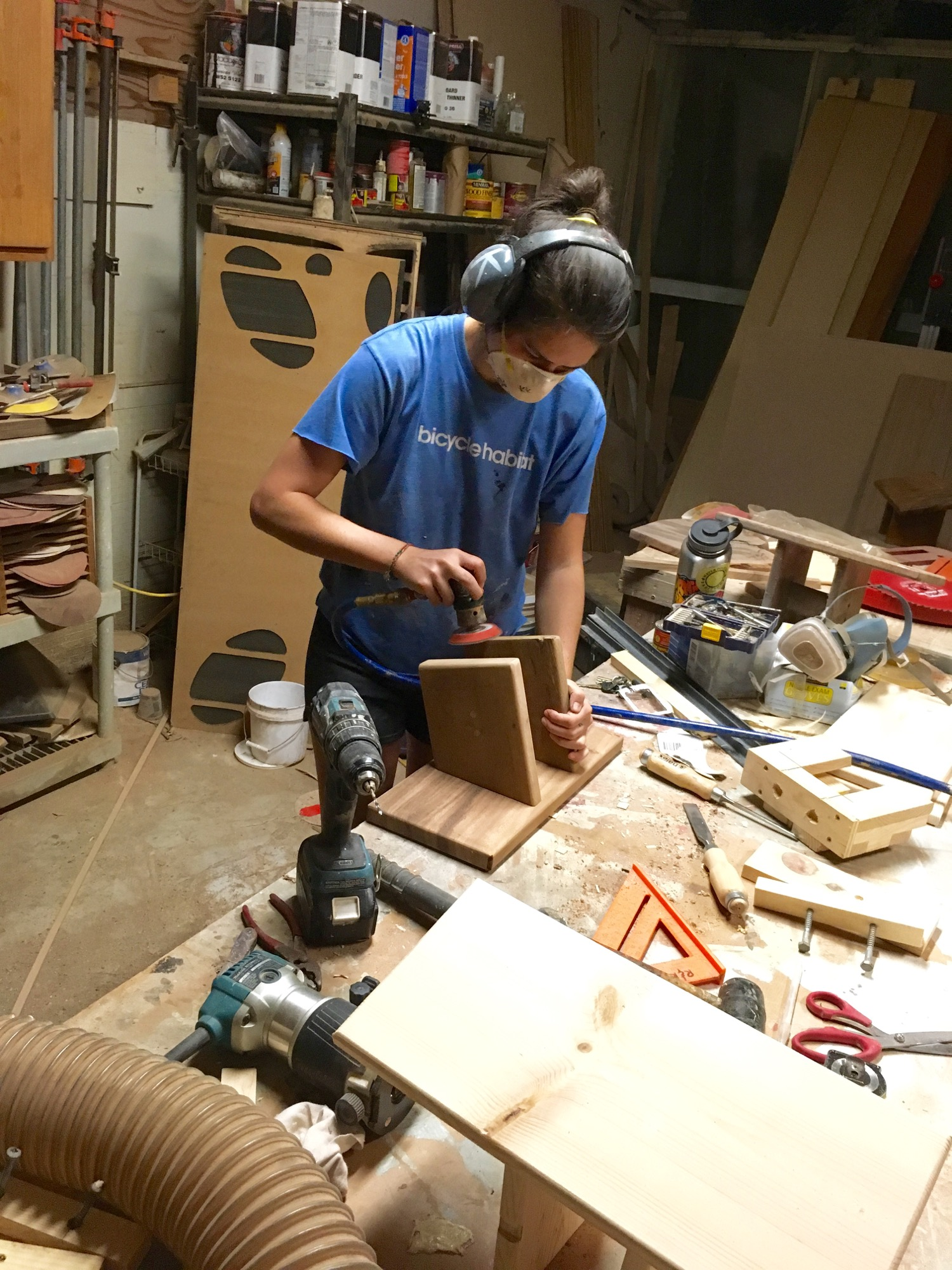 Finish sanding a monkeypod stool using a air-powered detailed sander.