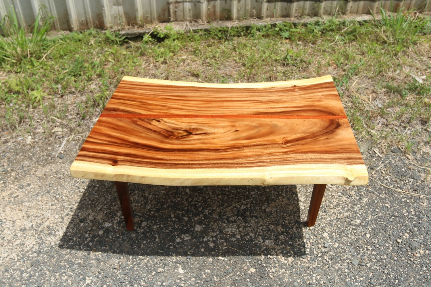 Monkeypod coffee table with curly koa strip down the center. Classic tapered four leg base.