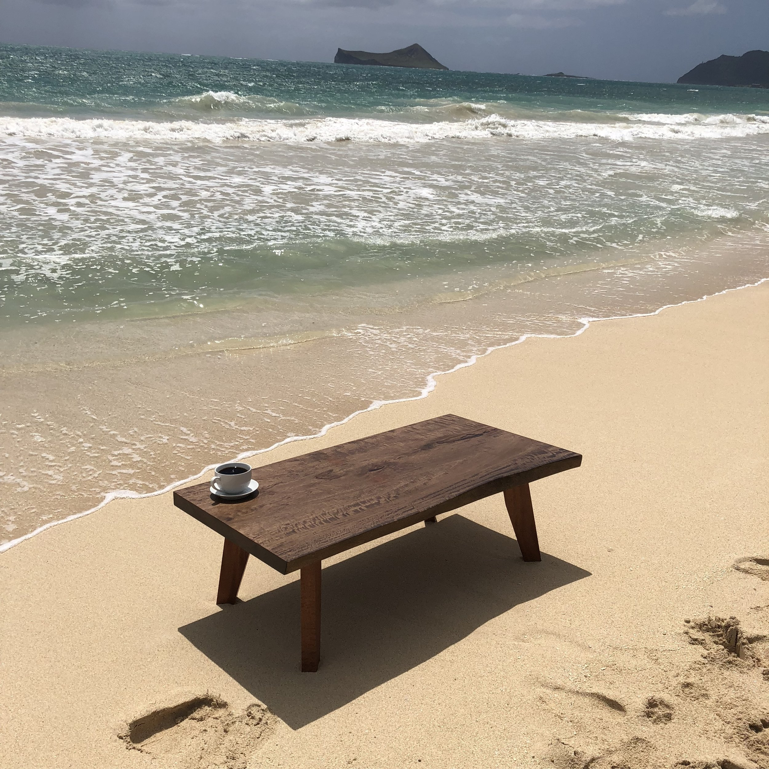 Mango coffee table stained ebony. Curly pommele legs with a midcentury design. Photo taken at Waimanalo Beach, about ten minutes away from the Rust & Root studio.