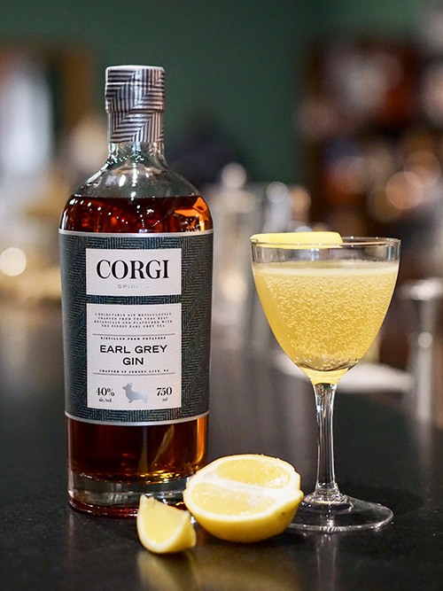 BRIT 75   1 oz Corgi Spirits Earl Grey Gin  0.5 oz fresh lemon juice  0.5 oz simple syrup (1 part sugar : 1 part water)  Sparkling wine  Lemon twist for garnish    Fill a shaker with ice, add gin, lemon juice, syrup and shake vigorously. Strain into a chilled champagne glass and top with sparkling wine. Add lemon twist.