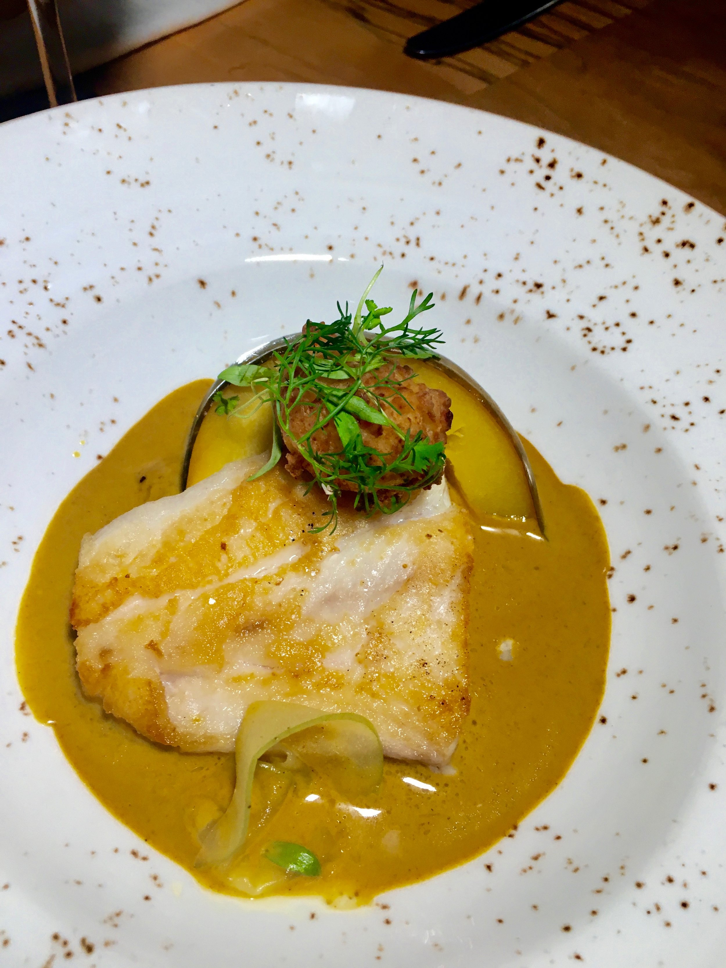 Roasted Florida red snapper in coconut curry with conch fritters and charred pineapple