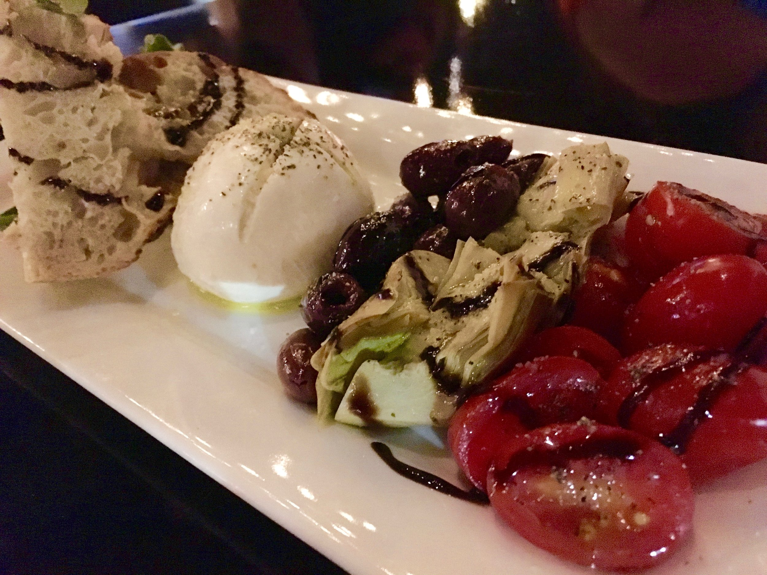 """MidiCi offers four presentations of """"artisan"""" burrata, which is a soft mozzarella cheese with a soft center. According to the menu, """"Each fresh burrata cheese is hand-formed and made from fresh milk gathered daily from local farmers."""" Here in Orlando, or back in L.A,? I'm curious where those farmers are. Still, this was delicious.Here the burrata is topped with a lemon vinaigrette and plated with artichoke hearts, grape tomatoes and kalamata olives ."""