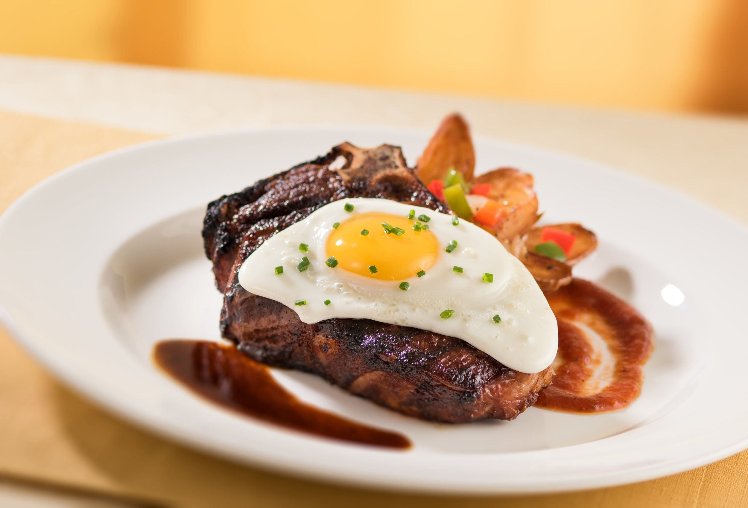 Capital Grille's bone-in dry-aged New York strip with fried egg, Lyonnaise potatoes and red jus