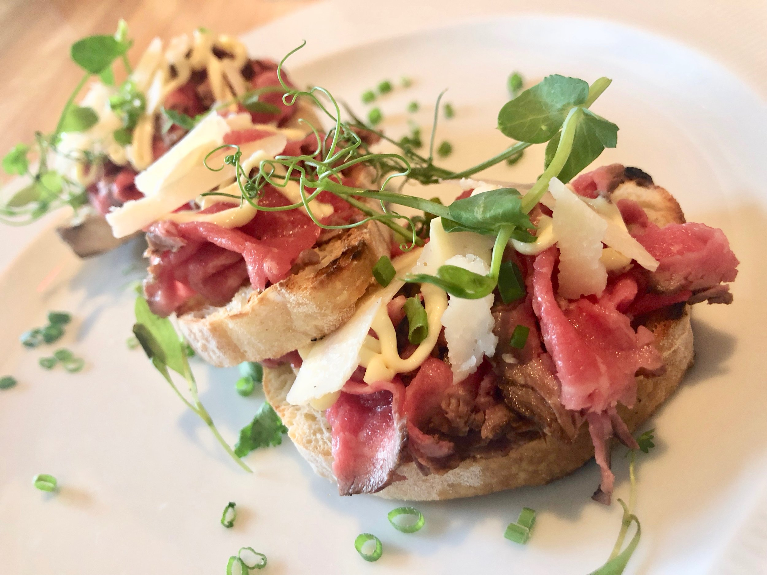 Ravello – Bruchetta Albese. Country bread topped with beef tenderloin, truffle aioli, lemon and parmesan. It's a meal, really. Gobble, then pack the rest to go.