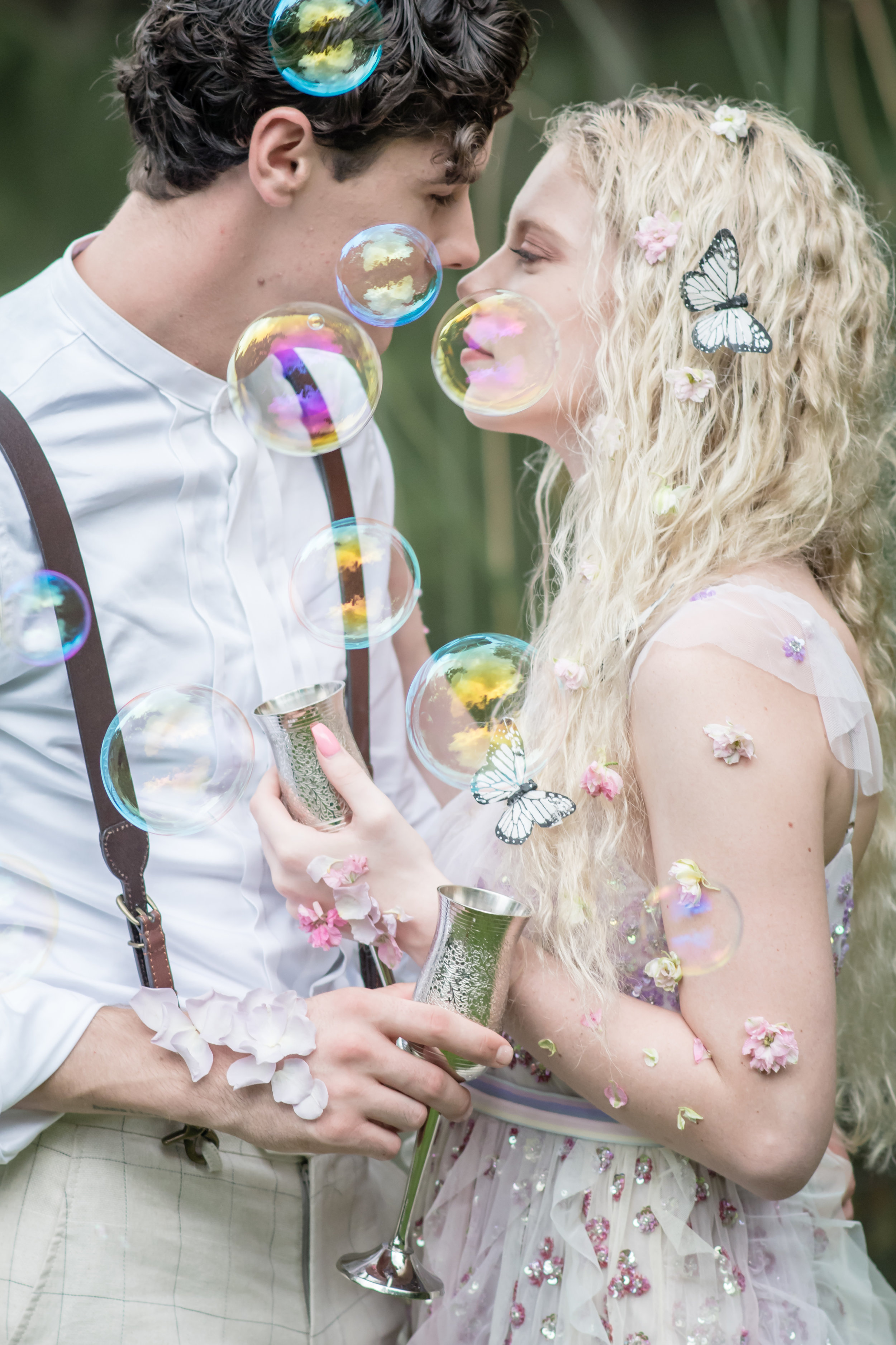 couple celebrating with champagne and bubbles in the forest bridal inspiration