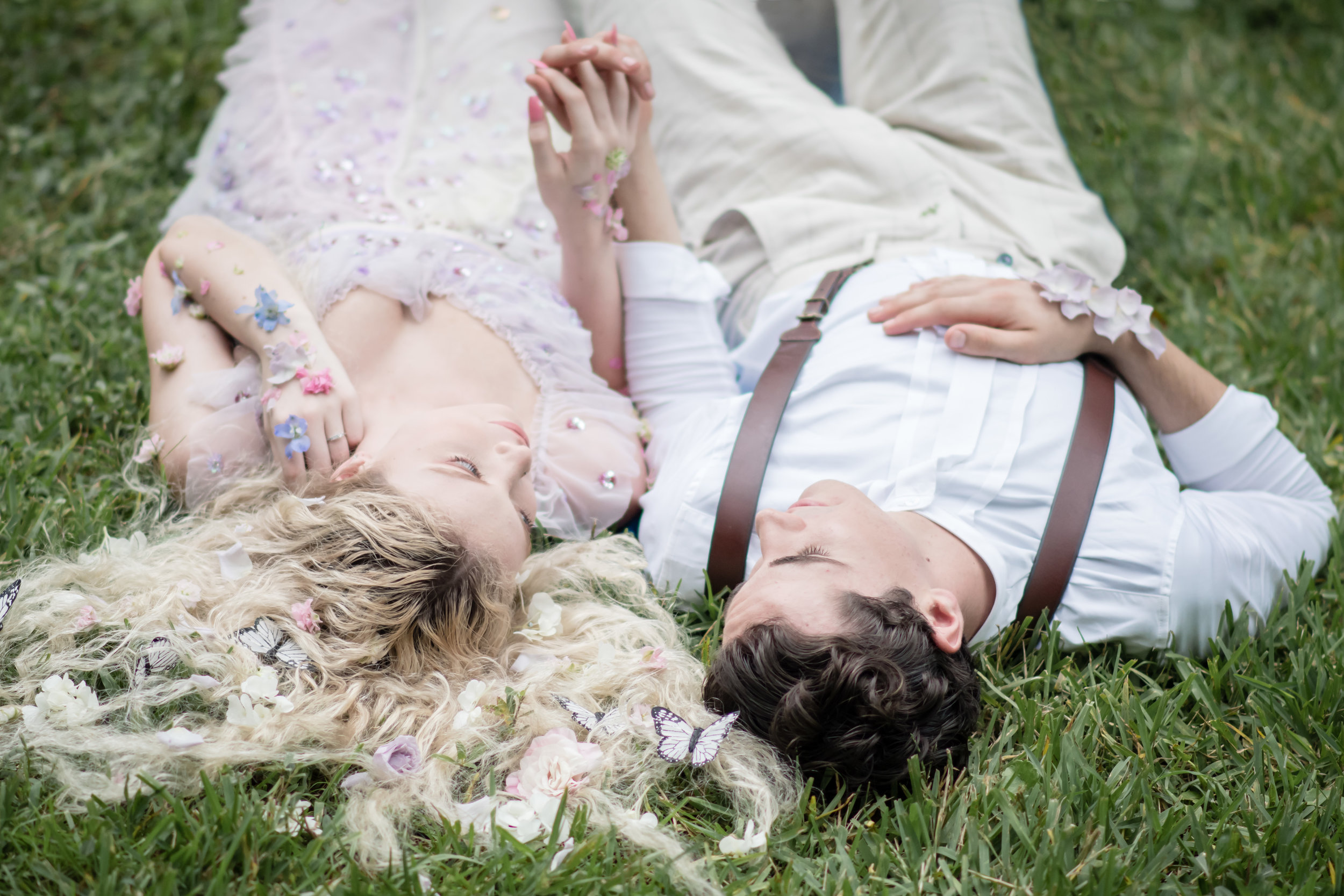 couple laying on the ground photos with florals on hair and skin