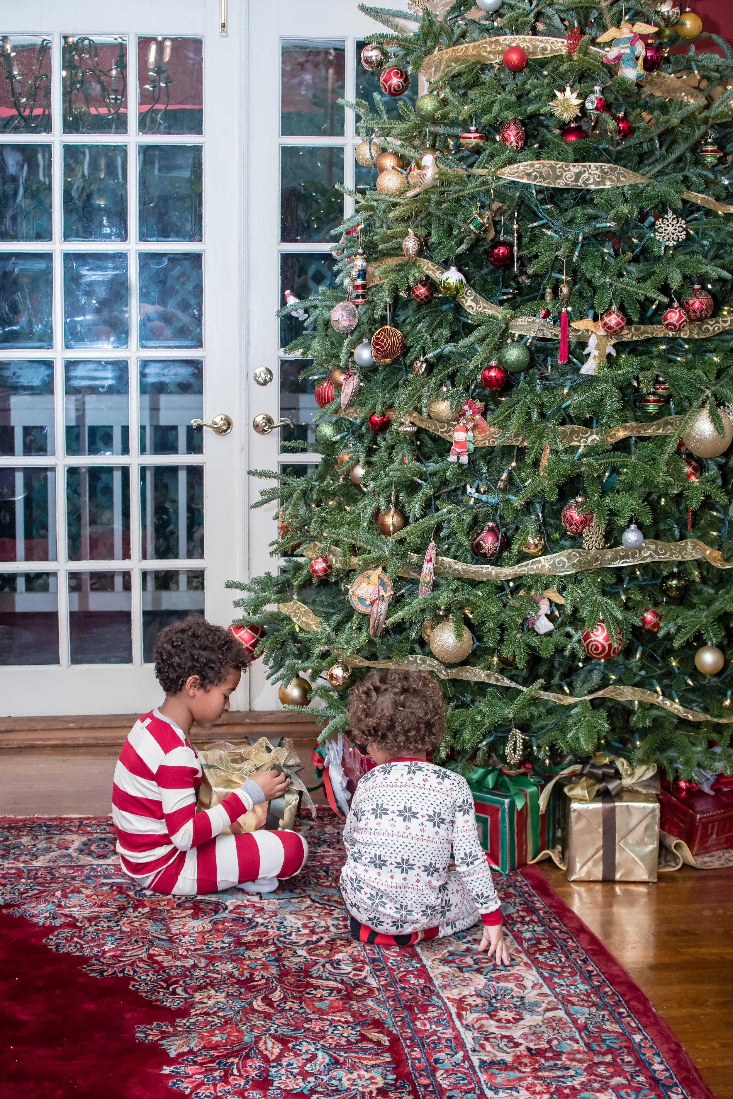 kids opening presents by the Christmas tree on Christmas Day Orlando Photographer Yanitza Ninett