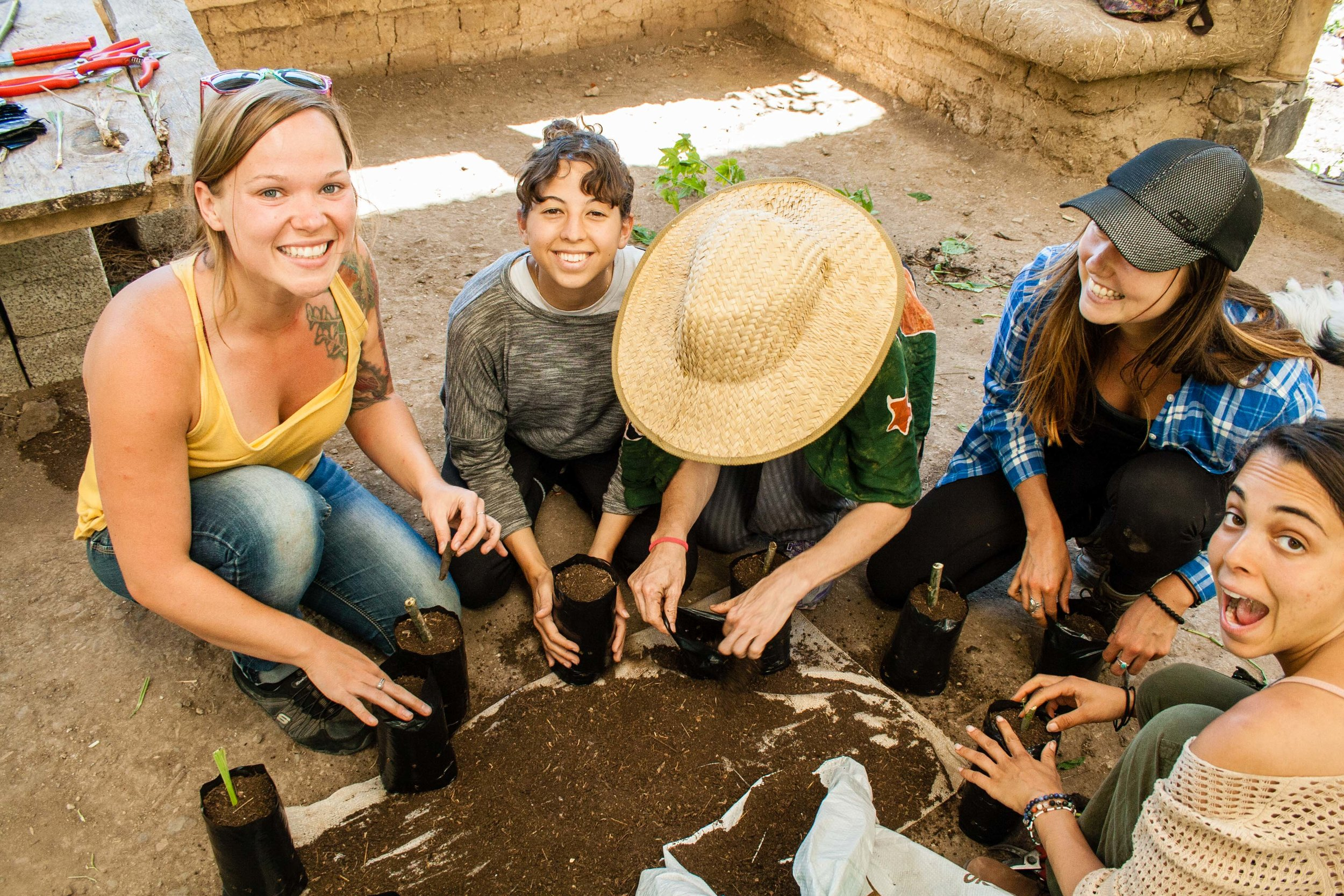 Happy participants smile at camera while preparing Permaculture garden at Atitlan Organics, permaculture design course, Lake Atitlan, Guatemala